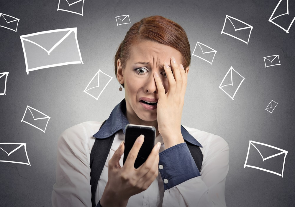 Woman frustrated by emails on phone, ITVibes